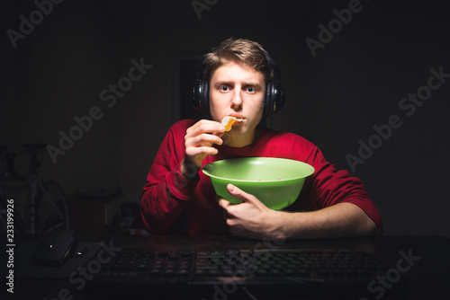Photo  Young man eats chips at home watching a video on the Internet on a computer and eating a snack