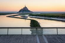 The Silhouette Of The Famous Mont Saint-Michel Tidal Island In Normandy At Sunrise And High Tide With The Still Waters Of The Couesnon River And The Wooden Footbridge Over The Dam In The Foreground.