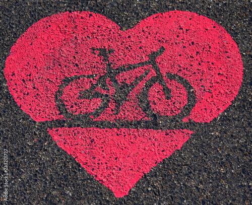 Leuchtendes, gespraytes herz auf einem Fahrradweg
