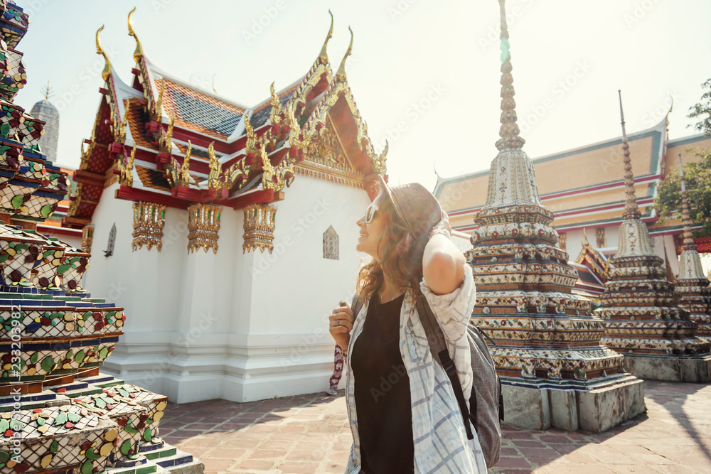 Fototapety, obrazy: Young beautiful happy smiling european woman in a hat and glasses at a buddhist temple in Bangkok traveling to southeast Asia