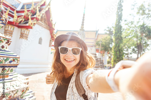 Fotografia  Young beautiful happy smiling european woman in a hat and glasses at a buddhist