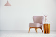 Leinwanddruck Bild - Pink armchair next to wooden table with plant in flat interior with lamp and copy space. Real photo