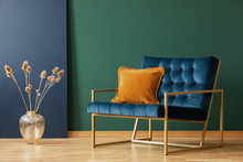 Brown Cushion On Blue Armchair In Green Living Room Interior With Flowers In Gold Vase. Real Photo