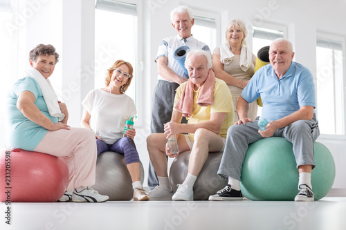 Happy senior people sitting on balls after physical classes in the studio Canvas-taulu