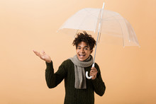 Portrait Of Teenage African American Guy Wearing Sweater And Scarf Standing Under Umbrella, Isolated Over Beige Background