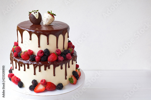 Two-tiered wedding cake in chocolate, with slices strawberries, raspberries, blackberry, decorated with figures of the bride and groom on a white background Fotobehang