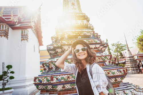 Stampa su Tela  Young beautiful happy smiling european woman in a hat and glasses at a buddhist