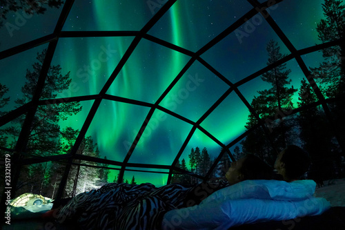 Fotografiet  CLOSE UP Young Caucasian tourist couple observing the night sky from a cool glass house in the Scandinavian wilderness