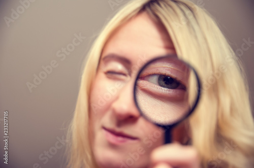 Fotografie, Tablou The woman with a magnifier in a hand