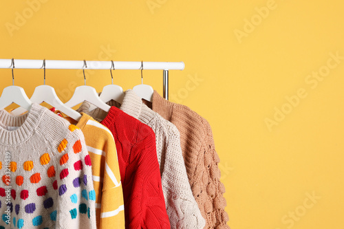 Fotografia  Collection of warm sweaters hanging on rack against color background