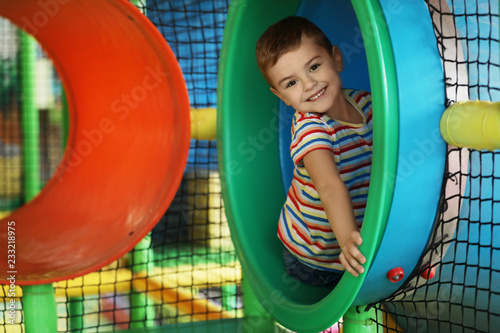 Photo Cute little child playing at indoor amusement park