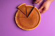 canvas print picture - Woman hands cutting a pumpkin pie. Purple background with copy space. Above view.