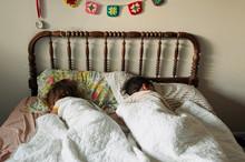 Siblings Sleeping In Bed Together