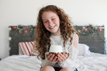 Pretty Girl Drinking Hot Chocolate On Bed With Christmas Decorations.