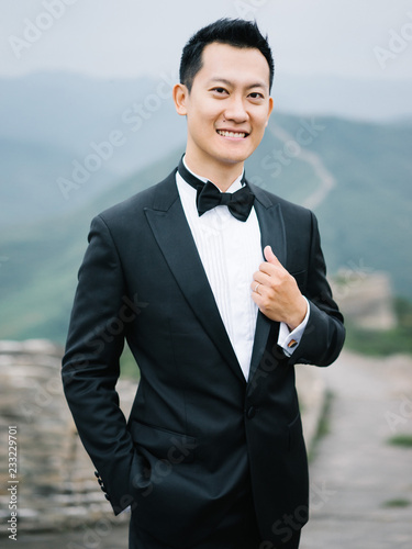 Stylish groom posing cheerful