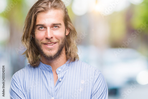 Fotografie, Obraz  Young handsome man with long hair over isolated background happy face smiling with crossed arms looking at the camera