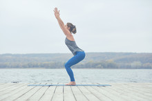 Beautiful Young Woman Practices Yoga Asana Utkatasana - Chair Pose On The Wooden Deck Near The Lake