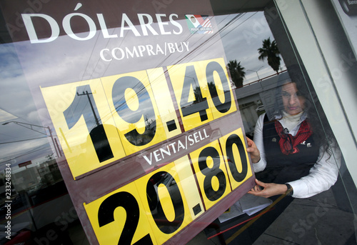 An employee places a board displaying the exchange rate of the