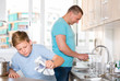 Smiling bou is washing dishes with his father together
