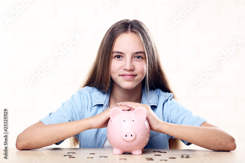 Fotografía  Young girl with pink piggybank and coins sitting at table