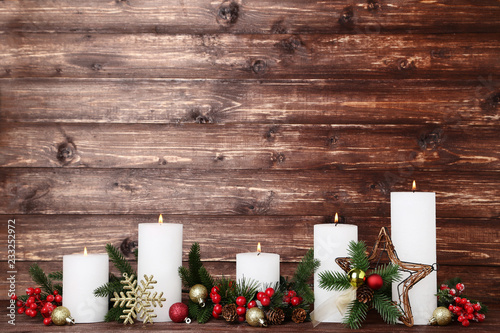Fotografía  White christmas candles with fir tree branches and baubles on brown background