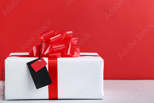 Fotografía  Black sale tag with gift box on red background