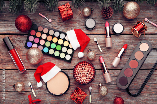 Fotografía  Makeup cosmetics with christmas baubles and santa hat on wooden table