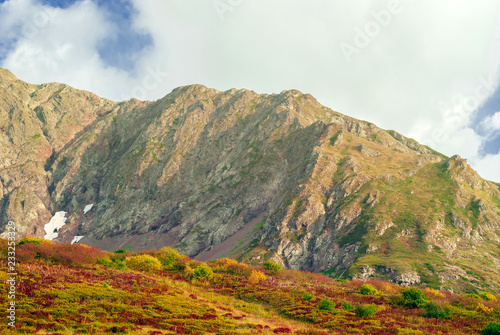 Foto op Aluminium Wit mountain landscape in the Caucasus with autumn bright vegetation in the foreground and rocky ridge in the background..