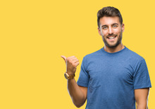 Young Handsome Man Over Isolated Background Smiling With Happy Face Looking And Pointing To The Side With Thumb Up.