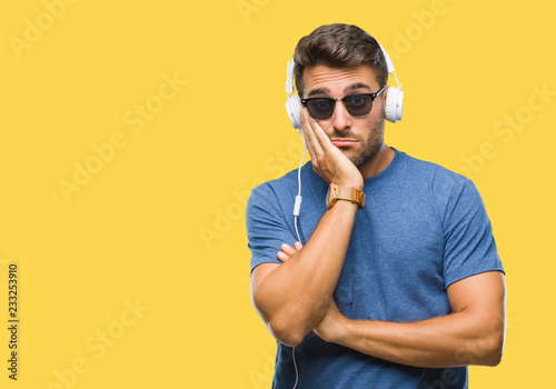Young handsome man wearing headphones listening to music over isolated background thinking looking tired and bored with depression problems with crossed arms. - 233253910