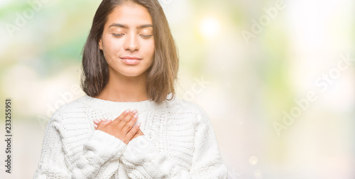 Obraz Young beautiful arab woman wearing winter sweater over isolated background smiling with hands on chest with closed eyes and grateful gesture on face. Health concept. - fototapety do salonu