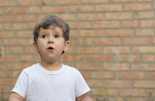 Happy Child Little Boy In White T-shirt Expresses Delight At A Blank Empty Brick Wall. Kid Near An Empty Brick Wall.