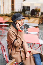 Portrait Of A Young Woman In Brown Coat And Gray Cap Using Phone. Smiling Cheerful Woman Is Sitting Outdoors At The Table In The Street Cafe At Bright Sunny Autumn Day