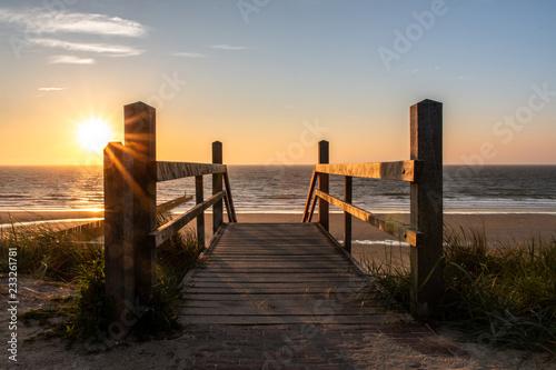 Canvas-taulu Strandaufgang im Sonnenuntergang