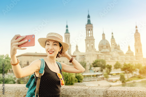 Fototapety, obrazy: asian tourist woman visiting Europe and making selfie with her smartphone at the background of famous Pilar Cathedral in Zaragoza, Spain