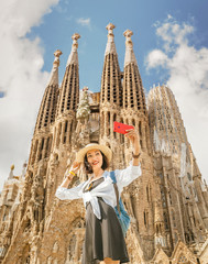 Fototapeta BARCELONA, SPAIN - 11 JULY 2018: Young asian woman making selfie photo on her smartphone in front of the famous Sagrada Familia catholic cathedral. Travel in Barcelona concept