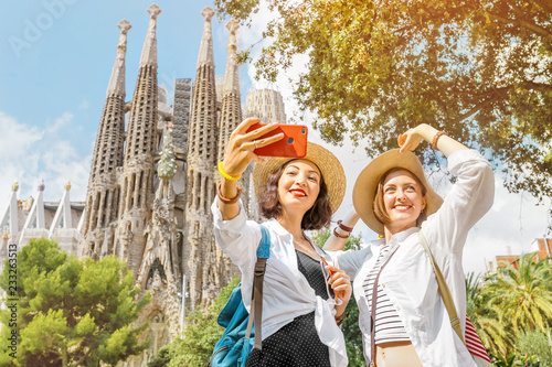 Foto auf Gartenposter Barcelona BARCELONA, SPAIN - 11 JULY 2018: Young girls friends making selfie photo on her smartphone in front of the famous Sagrada Familia catholic cathedral. Travel in Barcelona concept