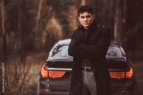 Fototapeta A stylish young man wearing a black coat with her arms crossed standing next to a luxury car in the autumn forest obraz