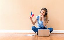 Young Woman With French Flag Using A Laptop Computer Against A Big Interior Wall