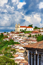 Top View Oof The Historic Ouro Preto City In Minas Gerais, Brazil With Its Famous Churches And Old Buildings With Hills In Background