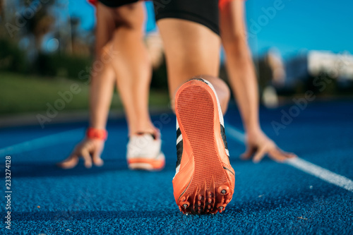 Fotografia Back view of a young male athlete at starting on blue running track