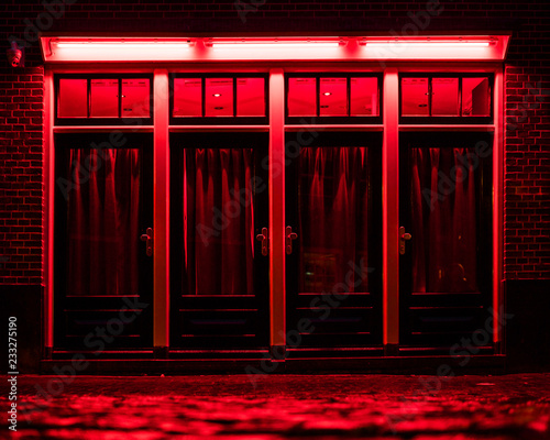 Red Light District in Amsterdam. Red boxes with curtains and wet Cobbles on the street - 233275190