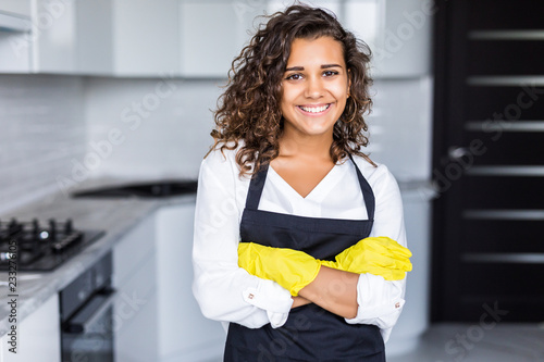 Fotografie, Obraz  Young american smiling woman wearing apron and rubber gloves, standing in kitche