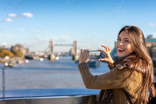 Fototapeta Portrait einer glücklichen Touristin in London beim Fotografieren der Tower Bridge auf ihrer Sightseeing Tour durch die Stadt obraz