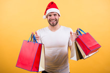 Online Christmas Shopping. Happy New Year. The Morning Before Xmas. Happy Santa Man On Yellow Background. Man In Santa Hat Hold Christmas Present. Delivery Christmas Gifts. Winter Holidays Sales