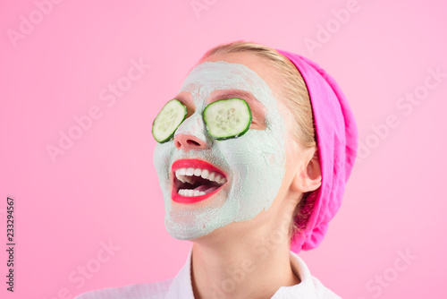 Fotografía  Beautiful young woman is getting facial clay mask at spa with cucumbers on eyes