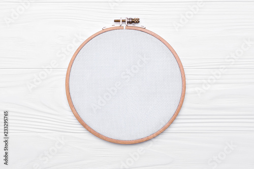 Fotografía Tools for cross stitch. A hoop for embroidery and canvas on white