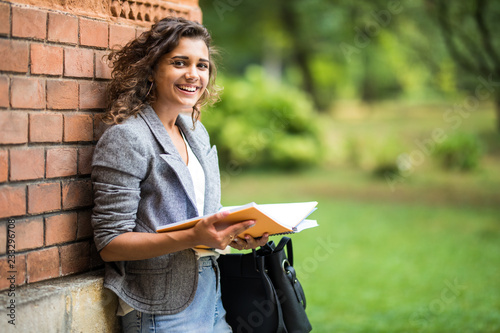Foto  Young latin american Woman reading book outdoors while leaning on the wall