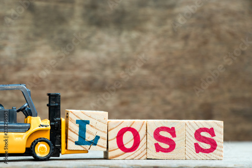 Fotografia  Yellow toy forklift hold letter block l to complete word loss on wood background
