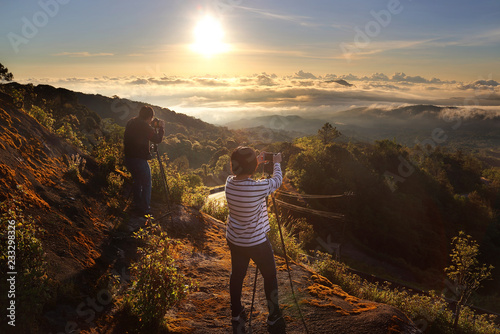Foto auf Gartenposter Schokobraun Male and Female Photographer they are taking photos beautiful scenery during sunrise time of Doi Tigers Head view point at Doi Inthanon National park,Chiang Mai in Thailand.